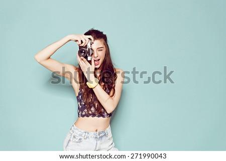 hipster photographer fashion stylish woman making photo using retro camera. Portrait on blue background