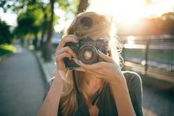 Hipster photographer using retro camera. Tourist girl capturing the moment