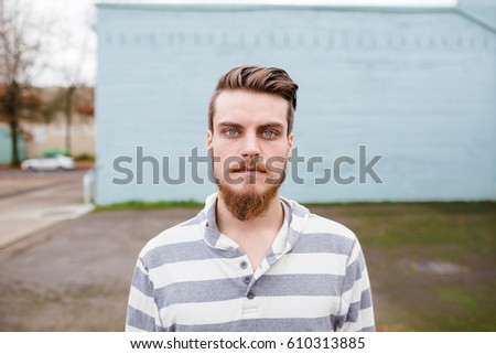 Hipster posing outdoors for the camera with a fashion forward style and a modern man appearance. - Shutterstock ID 610313885