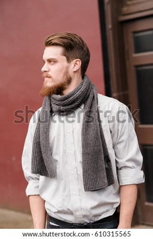 Hipster posing outdoors for the camera with a fashion forward style and a modern man appearance. - Shutterstock ID 610315565