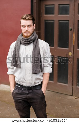 Hipster posing outdoors for the camera with a fashion forward style and a modern man appearance. - Shutterstock ID 610315664