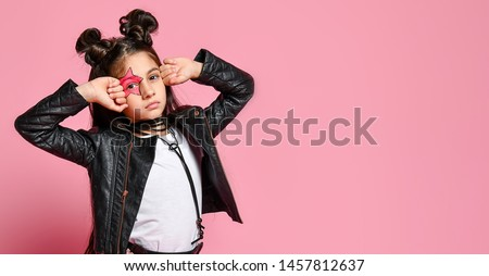 hipster punk girl - dressed in a leather jacket and skirt, black knee-highs and a white T-shirt, with a funny hairstyle and a makeup painted star on the face, points to the head #1457812637