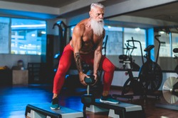 Hipster senior man training inside gym - Mature tattooed person having fun doing workout exercises in sport fitness club - Active elderly lifestyle and fit concept - Focus on face