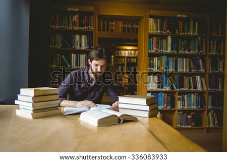 Hipster student studying in library at the university #336083933