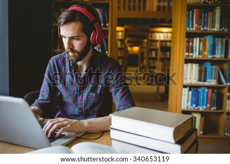 Hipster student studying in library at the university #340653119