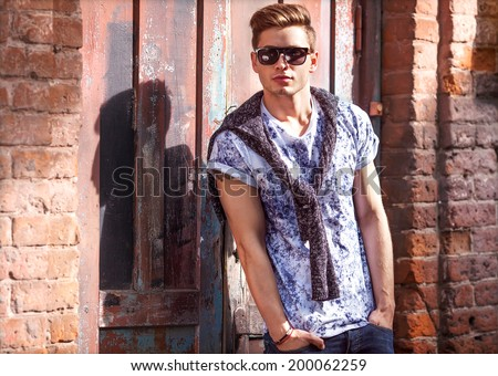 Hipster style guy. Fashion man standing near a wooden door