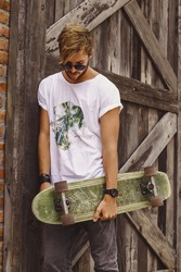 Hipster style guy. young skater man with a skateboard in casual wear