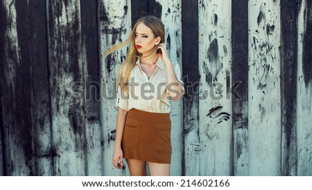 Stock Photo Hipster style. Portrait of young beautiful blond-haired girl in trendy clothes posing alone over black and white wall. Perfect skin and  make-up. Copy-space