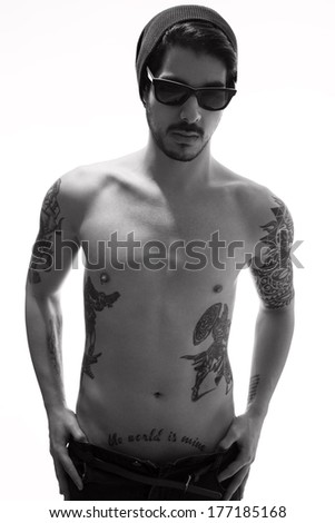 hipster style young man with several tattoos posing topless