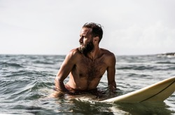 Hipster surfer sitting on his surfboard into the ocean water and waiting for a big wave - Fit bearded man training with surfboard to sea - Adventure and freedom concept doing water extreme sports