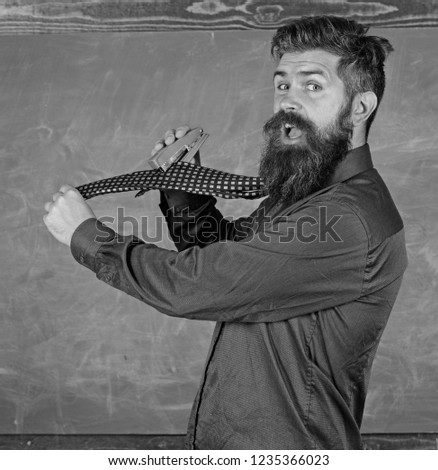 Hipster teacher formal wear necktie holds stapler. School stationery. Man scruffy use stapler dangerous way. Teacher bearded man with pink stapler chalkboard background. School accident prevention.