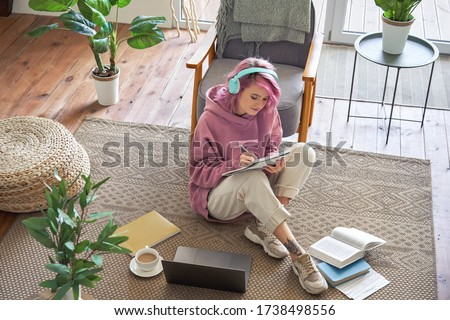 Hipster teen girl school college student pink hair wear headphones writing notes video conferencing on laptop sit in cozy room on floor working learning online in internet watching webinar. Top view.