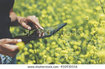 Hipster texting message on tablet or technology, mock up of blank screen. Girl using computer on yellow flowers background close. Female hands holding gadget mockup copy space for text message design #450930556