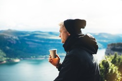 hipster tourist hold in hands mug of hot drink, lonely guy enjoy sun flare mountain in auto, happy traveler drink cup of tea on nature, vacation weekend concept on panoramic landscape