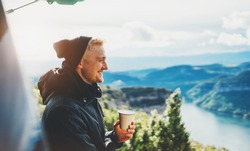 hipster tourist hold in hands mug of hot drink, lonely guy smile enjoy sun flare mountain in auto, happy traveler drink cup of tea on nature, vacation weekend concept on panoramic landscape