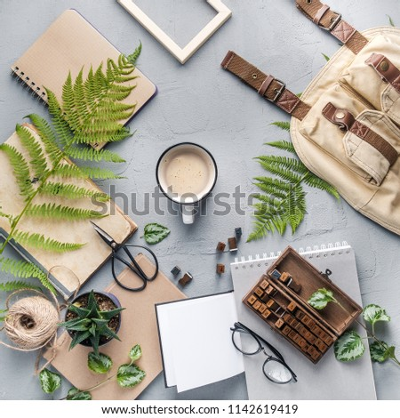 Hipster travel objects flatlay with book, plants, leaves, glasses, cards, coffee cup, frame. Creative work table for photographer, traveller, blogger. Working space surface top view
