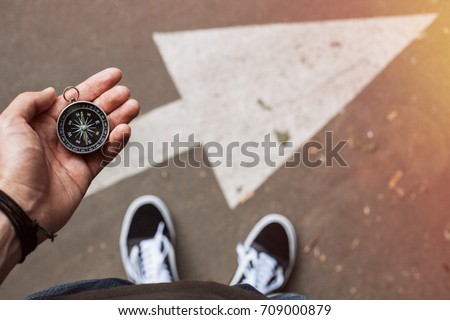 Hipster traveler holding compass in the hand making choice in what direction to go