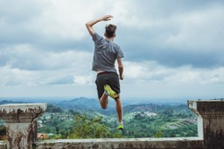 Hipster traveler jumping against the mountains, Bali