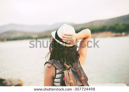 Hipster Traveler with backpack and outspread hands near sea at sunrise. Enjoying sun, deep breathing