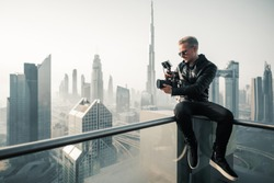 Hipster videographer / filmmaker sitting on a rooftop in Dubai at sunrise.