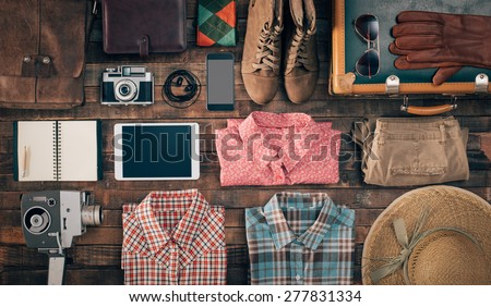 Hipster vintage accessories and clothing on a wooden table before packing, travel and vacations concept, top view