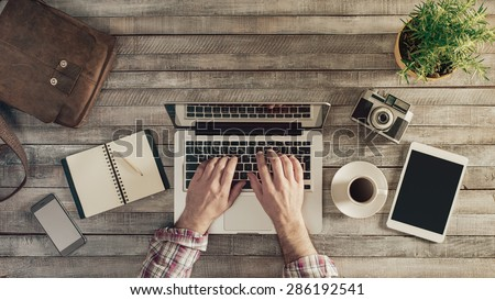 Hipster vintage wooden desktop top view, male hands typing on a laptop