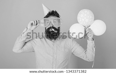 Hipster with bushy beard celebrating birthday. Bearded man posing in birthday cap with enormous glasses and bright balloons isolated on blue background. Man with trimmed beard blowing party whistle. #1343371382
