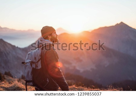 hipster with hat and beard wearing casual clothes during a colorful sunset hike  #1239855037
