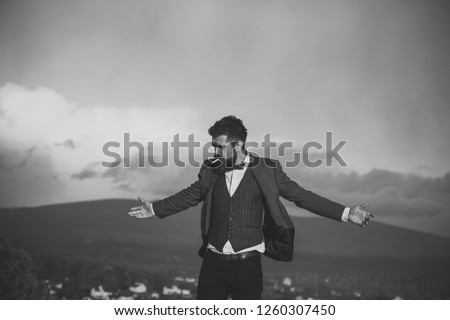 Hipster with stylish appearance in front of dramatic sky, skyline. Man with beard with scenery on background. Freedom concept. Guy with strict face in suit with bow tie feels free and smoking. #1260307450
