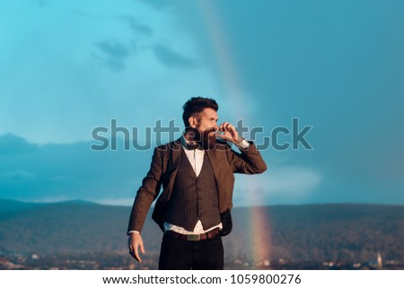 Hipster with stylish appearance smoking in front of sky with rainbow. Lord of world concept. Successful man with scenery on background. Guy with strict face in suit feels free and successful. #1059800276