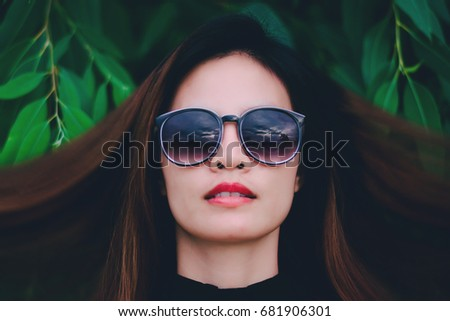 Hipster woman face wears black sunglasses on nature background.