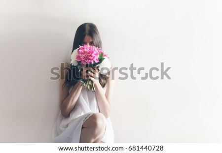 hipster woman in white dress holding pink bouquet of peonies in white room. boho bride with peony bouquet in front, relaxing in morning, space for text. spring girl with flowers #681440728