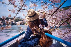 Hipster woman is sightseeing cherry blossom on the row boat while traveling during spring season at Chidorigafuchi boat parking inside the Kitanomaru Park in Tokyo, Japan.