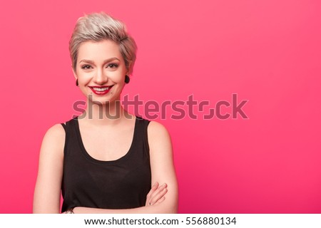 Hipster woman smiling against a pink background