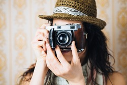 Hipster woman taking photos with retro film camera on vintage ornamental wallpaper.