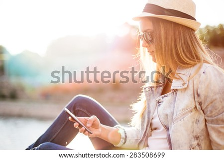 Hipster woman texting in sunset by the sea