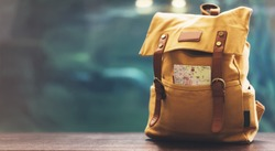 Hipster yellow backpack and map closeup. View from front tourist traveler bag on background blue sea aquarium. Person hiker visiting ocean museum in Barcelona on backdrop, blank blurred mock up