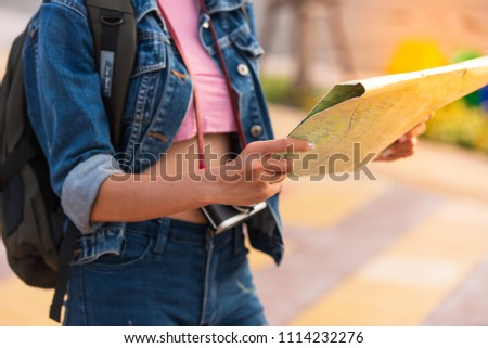 Hipster young girl backpack tourist hand holding a map for search and plan her tour.Woman traveler touring in the summer. #1114232276