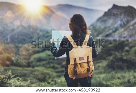Hipster young girl with backpack enjoying sunset on peak of foggy mountain, looking a map. Tourist traveler on background landscape panoramic view mockup, flare in trip Spain basque country, mock up