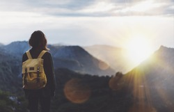 Hipster young girl with backpack enjoying sunset on peak of foggy mountain. Tourist traveler on background view mockup. Hiker looking sunlight in trip in Spain country, mock up text. Picos de Europa