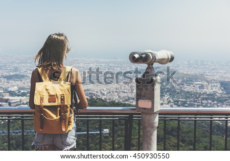 Hipster young girl with bright backpack looking on observation deck, tourist traveler on background panoramic view of the city, coin operated binoculars. Mock up for text message. Barcelona Tibidabo