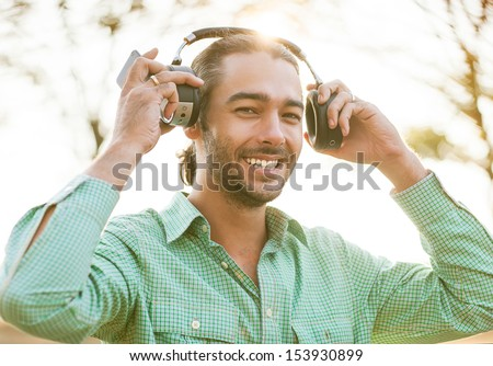 hipster young man listening to music on the street, takes headphones and smiling at the camera.