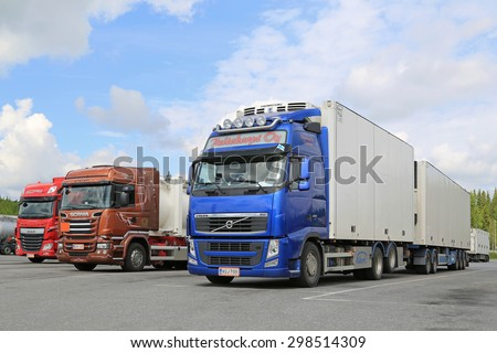 HIRVASKANGAS, FINLAND - JUNE 20, 2015: Volvo FH, Scania and DAF trucks at a truck stop on Midsummer Day. Road transport goes on throughout the Finnish celebration of Midsummer.