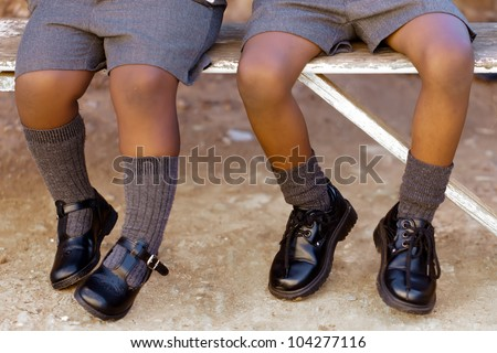 His and her school shoes, toughies on the step.