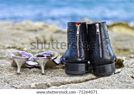 his and hers wedding shoes abandoned on the rocks while the bride and