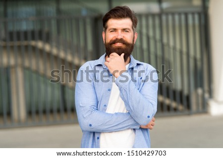 His beard needs a barber. Happy barber on urban background. Bearded man with shaped beard and mustache hair smiling before or after visiting barber. Mens barber and barbershop.