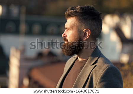 His bearded hair look styled. Bearded man outdoor. Bearded hipster in casual business style. Brutal guy wear mustache and beard on bearded face. Barbershop. Beard grooming.