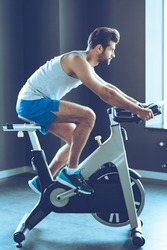 His favorite cardio workout. Side view full length of young handsome man in sportswear cycling at gym