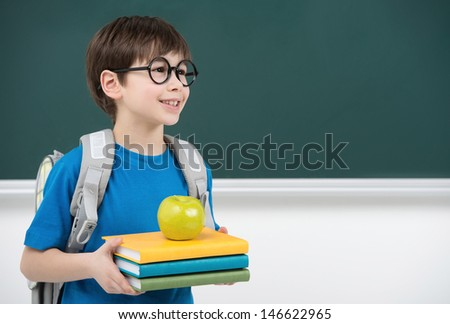 His first day at school. Cheerful little schoolboy holding the book stack and smiling while standing in front of blackboard