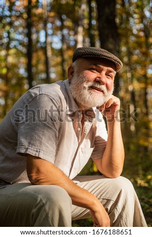 His new life as pensioner. Old pensioner relax in natue. Pensioner with grey beard hair in woods. Bearded man of pensioner age. Right to pension. Autumn of life.